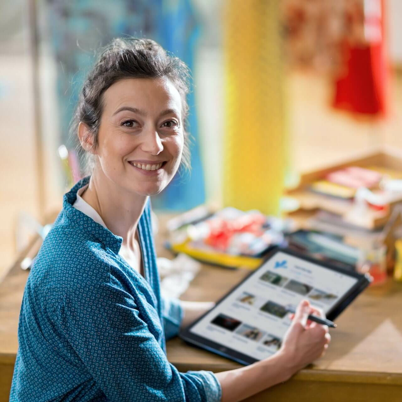 Smiling White woman working on iPad and sitting at desk in painting studio