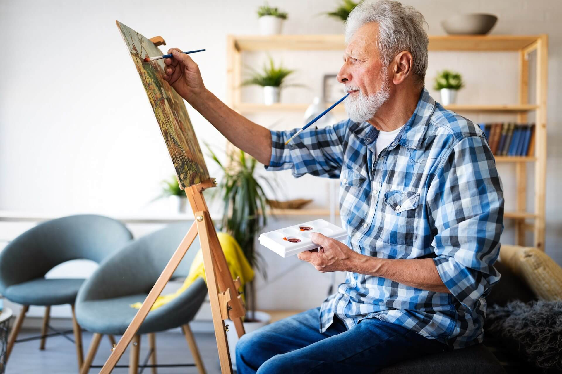 Older white man wearing blue plaid shirt painting on a wooden panel at an easel